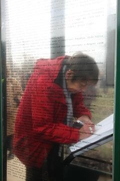 Örkény Angéla ír a telefonfülkében elhelyezett vendégkönyvbe