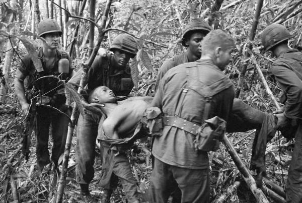 Soldiers of the 101st Airborne Division carry a wounded buddy through the jungle in May 1966. (AP Photo/Henri Huet)